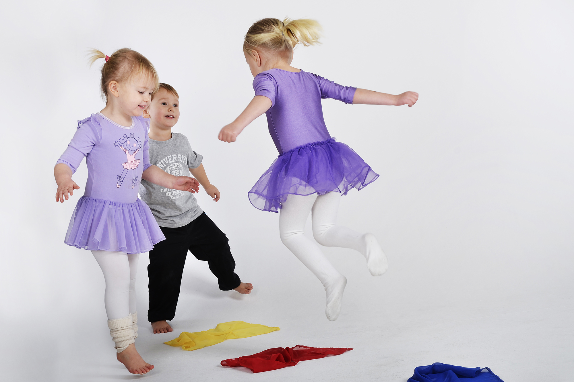 Tre barn hoppar och leker i ett rum